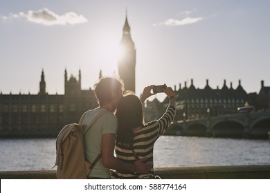 Tourist couple taking photo of Big Ben London with smart phone technology for social media at sunset