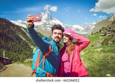 Tourist couple taking a selfie. Boy holding the phone. Beautiful scenic landscape in the back. Matterhorn. Switzerland 2017