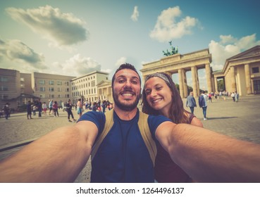 Tourist couple taking selfies smart phone Brandenburg Gate in Berlin Landmark having fun on adventure travel, Europe trip backpackers