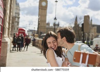 Tourist couple taking selfies smart phone Big Ben London Landmark kiss cheek having fun on adventure travel