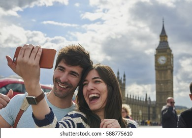 Tourist couple taking selfies smart phone Big Ben London Landmark having fun on adventure travel