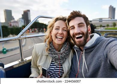 tourist couple travel selfie on open top tour bus in city