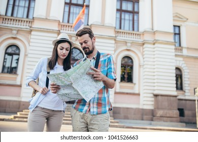 Tourist couple traveling and using map. Tourist couple exploring city.