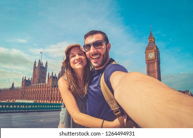 Tourist couple travelling in London taking selfie using smart phone with Big Ben London Landmark backgorund having fun on adventure travel backpacker