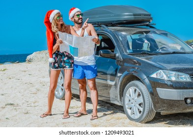 Tourist couple travels by car, with a santa hat and with a card in their hands, winter travel, freedom