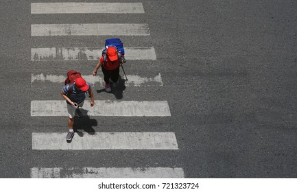 A tourist couple are walking across the crosswalk at the junction street of city, Pedestrian safety, Aerial view