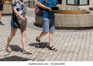 A tourist couple wearing shorts and t-shirts with sandals during summer walking in a pedestrian street using a tablet to guide them.