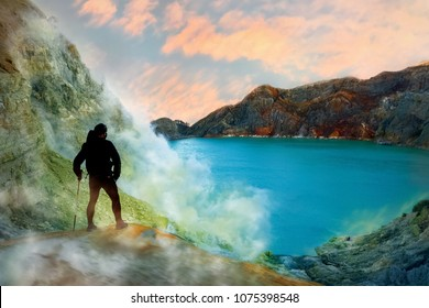 Tourist in the crater of a volcano. Sulfur rocks, volcanic blue acidic lake and pink sunrise. A dangerous journey into the crater of an active volcano. Gunung Ijen. Indonesia.