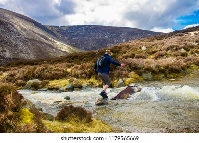 A tourist crossing the brook on the route to Mount Keen. Angus, Aberdeenshire, Scotland, UK.