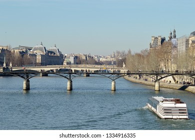 A tourist cruise boat heads along the River Seine in Paris to the famous bridges, Pont des Arts and the Pont du Carrousel with the historic Orsay Museum behind.