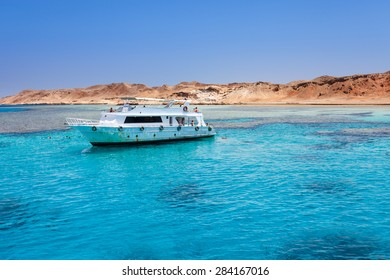 Tourist cruise boat with tourists in Red Sea next to island Tiran.
