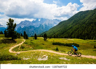 Tourist cycling in Cortina d'Ampezzo, stunning rocky mountains on the background. Man riding enduro flow trail. South Tyrol province of Italy, Dolomites.