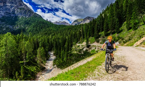 Tourist cycling in Cortina d'Ampezzo, stunning rocky mountains on the background. Female riding MTB enduro flow trail. South Tyrol province of Italy, Dolomites.