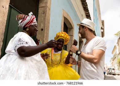 "Tourist dancing with local Brazilian woman ""Baiana"" in Pelourinho, Salvador, Bahia, Brazil"