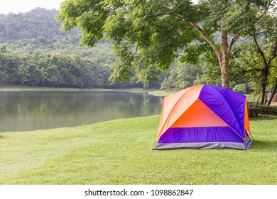 Tourist dome tent camping in forest camping site at lake side