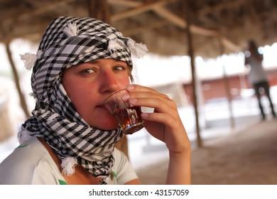 Tourist drinks Bedouin tea in Bedouin tent. Excursion in Egypt