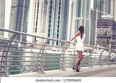 Tourist in Dubai marina looking at city skylines. Summer luxury holidays. soft focus