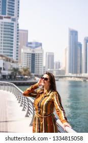 Tourist in Dubai marina looking at city skylines. Summer luxury holidays.