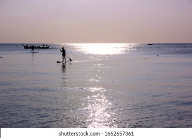 tourist are enjoy with surf board on sea in evening time before sun set.silhouette group of people in relax time with seascape,cloud sky nature  background.