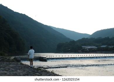 Tourist enjoying a sunset view by Katsura river in Arashiyama, Kyoto, Japan.
