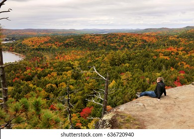 Tourist enjoys the view of Algonquin Park in fall, Ontario, Canada