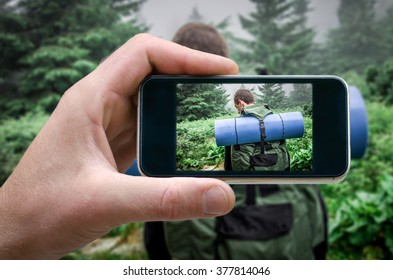 Tourist equipment Tourist walks in the jungle. view from the back. Tropical travel. photos from your phone, Selfi, the man photographs the on the phone (smartphone) side view