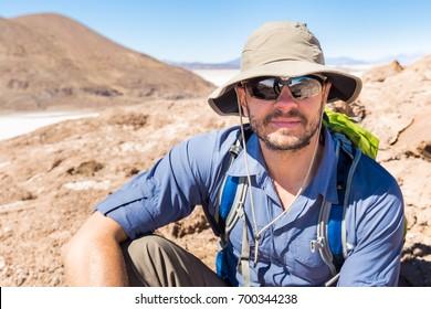 Tourist explorer  man guy portrait wearing sunglasses, sitting resting desert mountain volcano lava island,  Salar de Uyuni salt desert traveling, Bolivia backpacking journey.