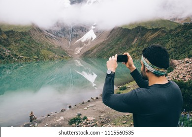 Tourist exploring natural environment of mountains covered clouds on modern smartphone device during wanderlust.Traveller shooting video of amazing nature in Salkantay on digital cellular