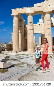 Tourist family mother and son posing against greek ancient temple ruins under blue sky in warm summer day, Athens, Greece