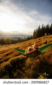 tourist family resting in a hammock in the mountains at sunset - Shutterstock ID 2009886827