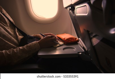 Tourist female hands while writing an application  at airplane seat near plane window with vintage light.