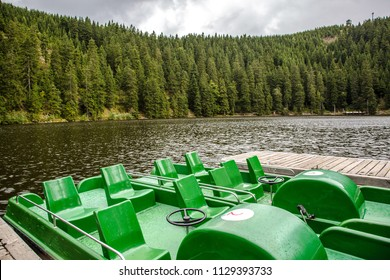 Tourist or fishing boats with widely spaced empty green seats on a mountain lake in a cloudy day with wind on the choppy water and forested slopes with conifers