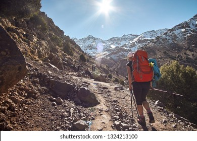 Tourist girl backpacker walking on the tourist path into the Atlas mountains in Morocco Africa