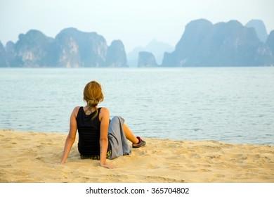 Tourist girl at beach, limestone view of halong bay, vietnam
