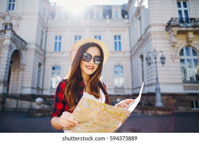 Tourist girl with brown hair wearing hat, sunglasses and red shirt, holding map at old European city background and smiling, traveling.