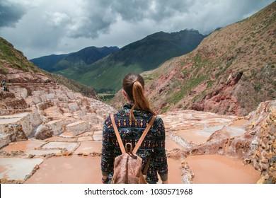 Tourist girl contemplating the salt ponds at  Maras Perú.