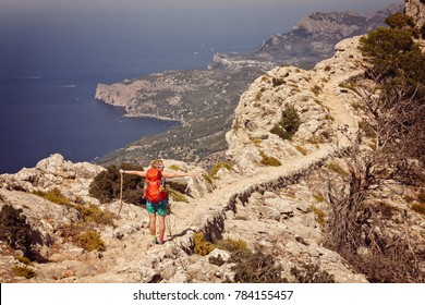 A tourist girl enjoys view of the sea from the mountain in Mallorca, Spain
