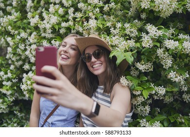 Tourist Girl Friends taking selfies smiling on summer fun travel adventure for social media with smart phone