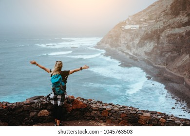 Tourist girl is happy to be on the end of long trekking route leading along cliff coastline with ocean waves from Cruzinha to to Ponta do Sol. Santo Antao Island, Cape Verde