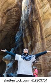 Tourist girl with hijab visiting Petra in Jordan