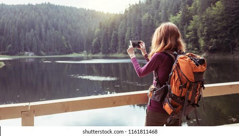 tourist girl making a photo shoot of  mountain lake synevyr. Carpathians,  Ukraine.