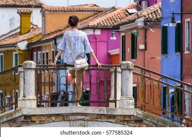 A tourist girl on the bridge on Burano Island Venice