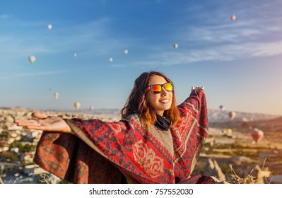 A tourist girl on a mountain top enjoying wonderful view of the sunrise and balloons in Cappadocia. Happy Travel in Turkey concept