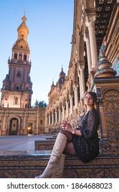 Tourist girl in Plaza de Espana, Spain Square in sunset, Seville, Spain