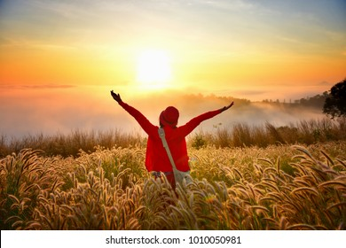 tourist girl with red sweater see the sunrise with foggy and yellow shine, PHU LAM DUAN, Loei, Thailand.