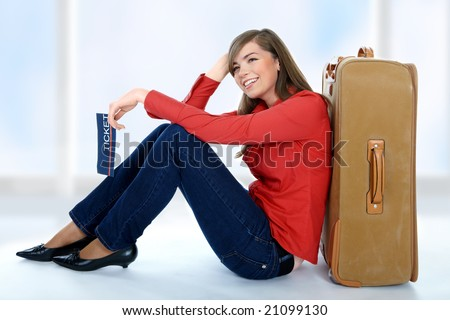 Tourist girl sitting on a suitcase with a ticket in her hand