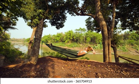 tourist girl sleeping on hammock, luang prabang, laos