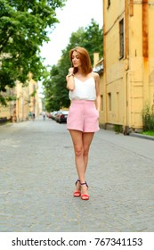 Tourist girl standing alone on empty street of old Europe city.  Elegant Thoughtful woman standing on road.