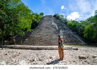 Tourist girl stands with her back against the background of Nohoch mul, mayan pyramid in Coba. Coba Archeological Area, Yucatan, Mexico