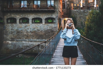 tourist girl stands on suspension bridge walking old historical city and takes photo with retro camera, cute young hipster woman enjoys weekend vacation in summer uses camera takes photos